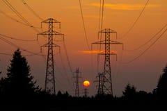 Cables de transmisión en puesta del sol Fotos de archivo libres de regalías