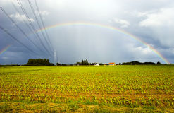 Cables de transmisión que entran en el arco iris Imagenes de archivo