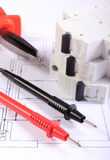 Cables of multimeter and electric fuse on construction drawing Royalty Free Stock Image