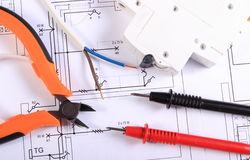 Cables of multimeter, pliers, electric fuse and wire on construction drawing royalty free stock photos
