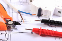 Cables of multimeter, pliers, electric fuse and wire on construction drawing Royalty Free Stock Photo