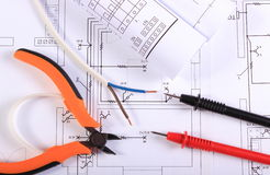 Cables of multimeter, pliers, electric wire and construction drawing Stock Images