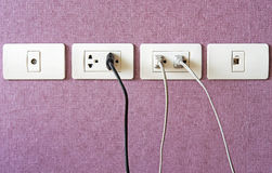Cables plugged in a white electric outlet mounted on pink wall Stock Photos