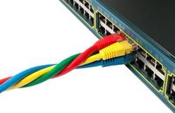 Cables torcidos de la red de Ethernet conectados con el eje Imagenes de archivo
