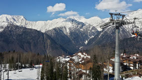 Cableway and cottage village in the snowy mountains of the Caucasus Royalty Free Stock Images