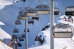 Cableway krzesła dźwignięcia z narciarkami i snowboarders na niebieskiego nieba tle Zdjęcia Royalty Free