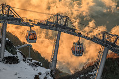 Cableway lift gondola cabins on cloudy mountain sunset background beautiful winter scenic landscape Stock Photos