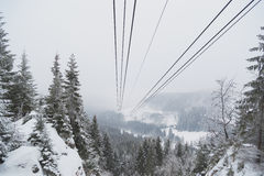 Cableway in the mountains in winter. Perspective view of the mountain woods and rope ropeway Stock Image