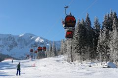 Cableway and skiers  on a sunny day on slopes in the ski resort Royalty Free Stock Photo