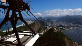 Cableway som kommer upp kullen med sikt av Rio de Janeiro lager videofilmer