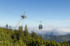 Cableway to Snezka with clouds in the background Stock Images