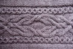 Cabling pattern on puce knitted fabric. From above Royalty Free Stock Images