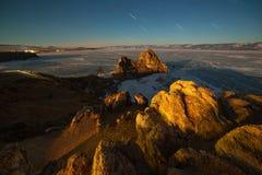Cabo Burhan Rock Shamanka iluminado por el claro de luna en la isla de Olkhon en el medio del lago Baikal en el fondo estrellado fotos de archivo libres de regalías