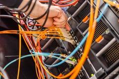 Cabo da fibra de Plugging High Speed do coordenador do homem a TI no interruptor de rede fotografia de stock