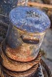 Cabo de aço corroído Rusty Iron Bollard With Coiled golpeado velho fotografia de stock
