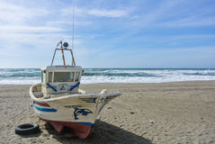 CABO DE GATA, SPAIN - FEBRUARY 9, 2016: A colored fishing boat at the shore of national park Cabo de Gata. Near Almeria Andalusia, Spain and sea waves on the Stock Photos