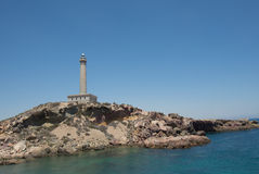 Cabo de Palos Lighthouse on La Manga, Murcia, Spain. Faro de Cabo de Palos, Murcia, Spain. Lighthouse atop a small peninsula in the mediterranean sea between stock images