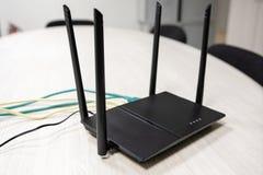 Cabo dispersado na tabela no router com Internet da casa na sala fotos de stock royalty free