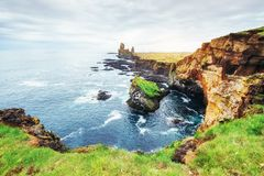 Cabo Dyrholaey em Islândia do sul Altura 120 m, e ilha média do monte com uma abertura da porta Imagens de Stock Royalty Free