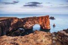 Cabo Dyrholaey em Islândia do sul Altura 120 m, e ilha média do monte com uma abertura da porta Foto de Stock
