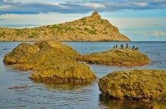 Cabo e grandes rochas na baía com um céu nebuloso bonito no Mar Negro em Crimeia, Novy Svet Fotos de Stock Royalty Free