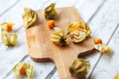 Cabo-goosberries fresco em uma corte-placa de madeira fotos de stock