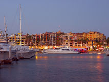 Cabo Marina at night. Beautiful white luxury yachts at Cabo San Lucas Baja Mexico.  Photo taken at dusk, with a trace of natural light plus all the lights from Stock Photography