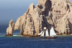 Cabo Rocks and Sailboat. Sailboat rounding rocks at the point of Baja Mexico Stock Image