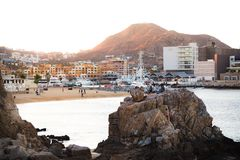 CABO SAN LUCAS, BCS, MEXICO - FEB 02, 2017: Group of youth spending the late afternoon by the public beach near the stock photography