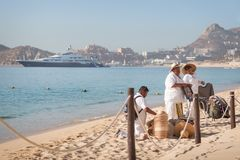 Cabo San Lucas, BCS, Mexico - 11 februari, 2017: Mexicaanse venters die goedkope goederen en trinkets op het strand in Cabo San v stock fotografie