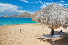 Cabo San Lucas Beach Relaxation. Cabo San Lucas, Mexico beach relaxation with palapa, relaxing chaise, no people.  Aqua blue ocean with mountain and clouds Royalty Free Stock Photo