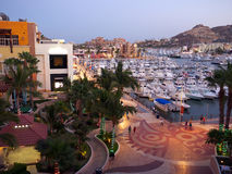 Cabo San Lucas, Marina at night. General view of the Cabo San Lucas Marina at dusk with all white fishing boats in the harbor and the boardwalk. Modern royalty free stock photos