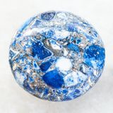 Cabochon from pressed Lazurite stone on white. Macro shooting of mineral rock specimen - cabochon from artificial pressed Lazurite stone on white marble Royalty Free Stock Photography