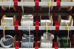 Cabos brancos elétricos diferentes O fio fere-se em skeins e em anéis Os fios elétricos cabografam amostras dos produtos na loja imagens de stock royalty free