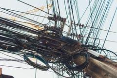 Cabos de fios desarrumados loucos do caos em polos elétricos fotografia de stock
