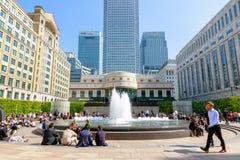 Cabot Square in Canary Wharf pakte met mensen in die van de zon genieten Stock Afbeeldingen