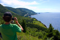 Cabot Trail. Teenage boy taking a digital picture of the winding road of the Cabot Trail in Nova Scotia, Canada Stock Photos