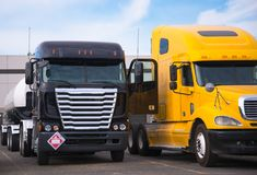 Different models of trucks are standing next to each other in pa. Cabover and bonnet semi trucks of different colors, models and designs for different uses for Stock Images
