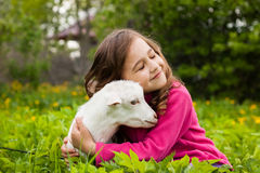 Cabra del abarcamiento de la niña pequeña en jardín Foto de archivo