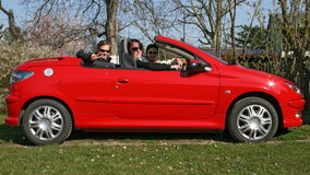 Cabrio girls. Three young girls with sunglasses driving around with red cabriolet Royalty Free Stock Image