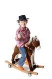 Cabrito adorable que monta un caballo del juguete Imágenes de archivo libres de regalías