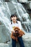 Cabrito asiático que juega con el perro de caniche Imágenes de archivo libres de regalías