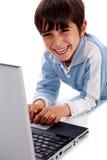 Cabrito caucásico sonriente lindo con la computadora portátil Fotos de archivo
