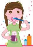 Cabrito de la muchacha que aplica Teeth_eps con brocha Imagen de archivo libre de regalías