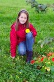 Cabrito de la muchacha que presenta con una flor en un prado Imagen de archivo