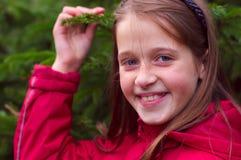 Cabrito de la muchacha que sonríe y que presenta cerca del árbol verde Imagen de archivo libre de regalías