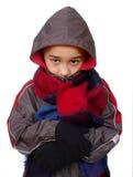 Cabrito en la ropa del invierno que mira a escondidas a través del capo motor Imagen de archivo