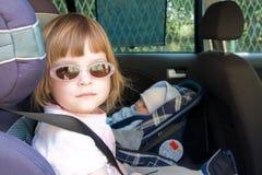 Cabrito en un asiento de coche de seguridad Imágenes de archivo libres de regalías