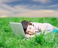 Cabrito lindo con la computadora portátil en prado verde Foto de archivo libre de regalías
