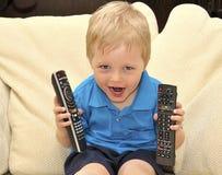 Cabrito lindo que ve la TV, sentándose en silla foto de archivo libre de regalías